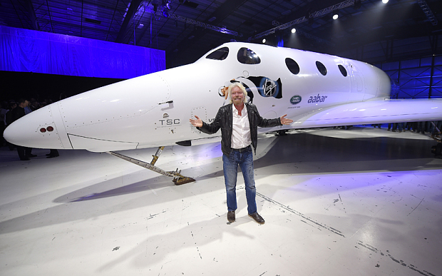 Sir Richard Branson poses in front of Virgin Galactic's SpaceShipTwo space tourism rocket after it was unveiled, Friday, Feb. 19, 2016, in Mojave, Calif. The company is preparing to resume flight testing for the first time since a 2014 accident destroyed the original and killed one of its two pilots.
